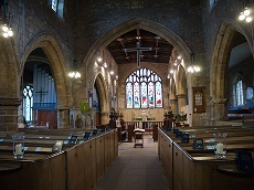 The present church interior looking towards the Victorian east window with Georgian box pews and chantry chapels to left and right